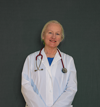 Photograph of the doctor wearing a lab coat and stethoscope, smiling.